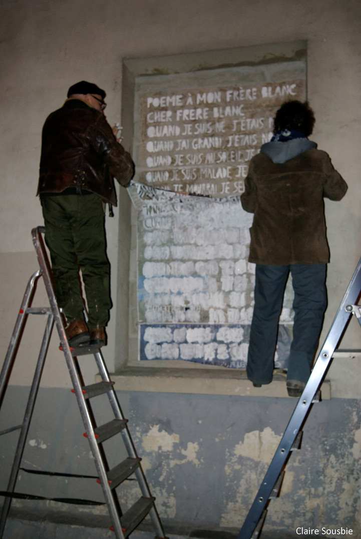 """Cyrille et Paule détachent le pochoir qui a servi à peindre """" Poème à mon frère blanc """" de Léopold Sédar Senghor :"""