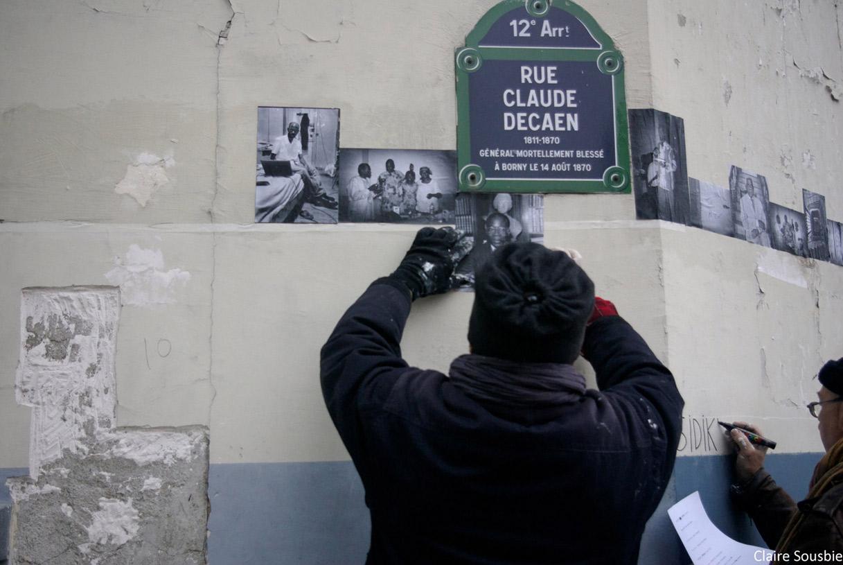 Remy encollant des photos mémoire du lieu prises par Claire Sousbie et Jérome Barbosa avant l'expulsion - Cyrille inscrivant en frise tous les prénoms des derniers occupants de la MEEAO