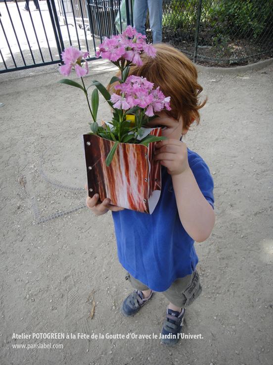 Philémon caché derrière son Potogreen réalisé lors de la Fête de la Goutte d'Or - Atelier Potogreen par Paule Kingleur / Paris Label, invité par le Jardin l'Univert