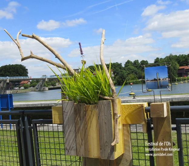 Paule Kingleur présente une installation de bois flottés de Seine avec plantes en jardinières recyclées et photos au chemin de halage des écluses d'alfortville pour le Festival de l'Oh 2014